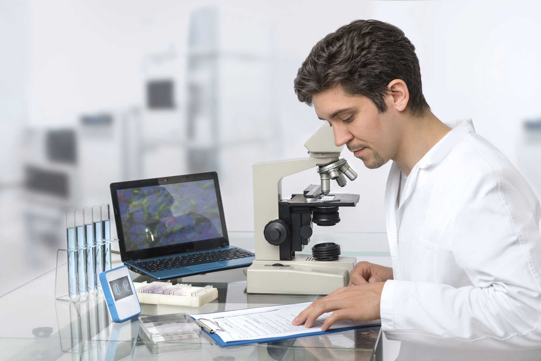 male researcher looking over notes in lab